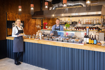 Counter service at modern bistro with smiling waiters serving food – happy business owners in small restaurant with open kitchen inviting people inside for food tastings  – catering service
