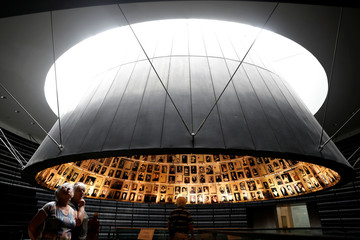 People look at pictures of Jews killed in the Holocaust during a visit to the Hall of Names in the Holocaust History Museum at the Yad Vashem World Holocaust Remembrance Center in Jerusalem, as Israel's annual Holocaust Remembrance Day begins tonight
