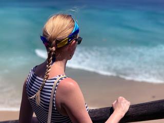 Femme portant u ntop et un bandana bleu devant une mer turquoise