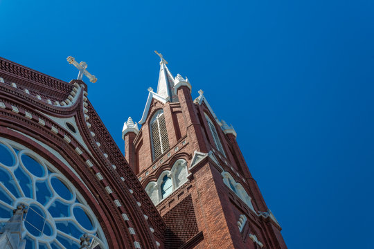 Beautiful details of steeples and rose window, Gothic Revival church, red brick white crosses, blue sky, horizontal aspect