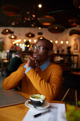 Warm toned portrait of pensive African-American man using laptop sitting at table in cafe