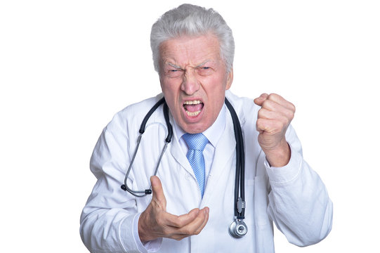 Portrait of angry senior male doctor with stethoscope isolated