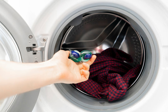persons hand put special cleaning pod or capsule in the washing machine with dirty cloth