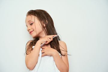 Smiling little preschool girl with wet hair photographed against white background wrapped in white towel while brushing her hair by drawing a comb through wet hair