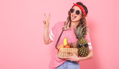 Portrait of a girl with healthy food, fruits, on a pink background