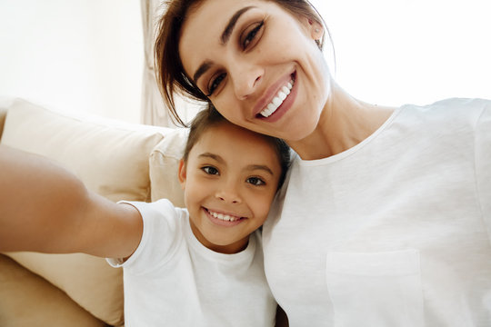 Family. Love. Mom and daughter in pajamas are hugging, looking at camera and smiling while doing selfie at home