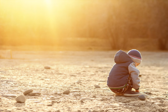 A six-year-old boy with autism sits on the ground alone at sunset. Lonely little child playing with stones outside. The concept of autism and loneliness. Copy space for your text. Setting sun.