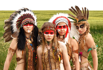 Four proud Indians pose outdoors in front of a camera. They dress up in traditional Indian costumes with  feathered headdresses and painted faces. Behind them a large prairie field.