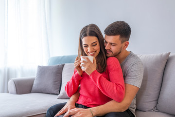 Beautiful young couple is talking and smiling while sitting on sofa at home. Woman is holding a cup. Cheerful beautiful young couple sitting and hugging on sofa at home