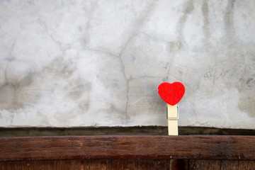 Red heart wooden clip with space on grey cement wall background, love and valentine concept