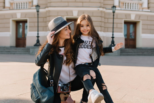 Graceful woman with camera and leather bag looking at daughter, posing on the street in sunny day. Cheerful long-haired girl sitting on mother's knee and playfully smiling.