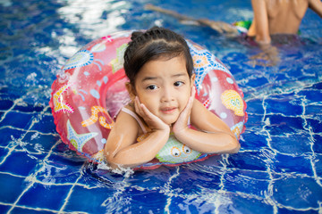 cute little girl feel happy play and swimming at swimming pool , sunny day and soft focus. Fototapete
