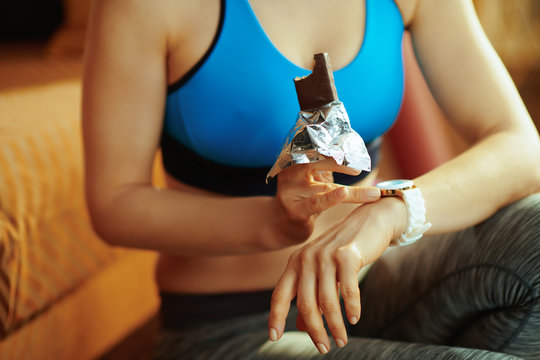 Closeup on sports woman with protein bar using smart watch