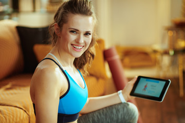 happy woman watching fitness videos on internet via tablet PC