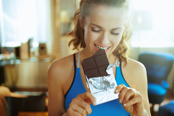 smiling young sports woman in modern house biting chocolate bar