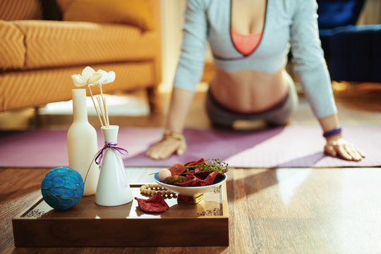 Closeup on tray with fragrant stuff and woman doing yoga