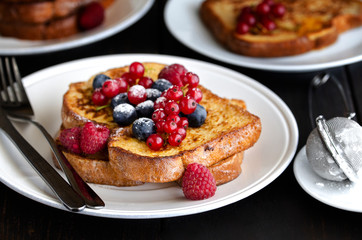 Traditional French toast with berries: blueberries, currant, raspberries  and icing sugar for perfect  sweet breakfast. Delicious dessert background.