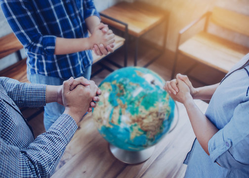 Three people standing and pray to God for the world with blurred world globe on wooden table, Christian background for great commission concept.