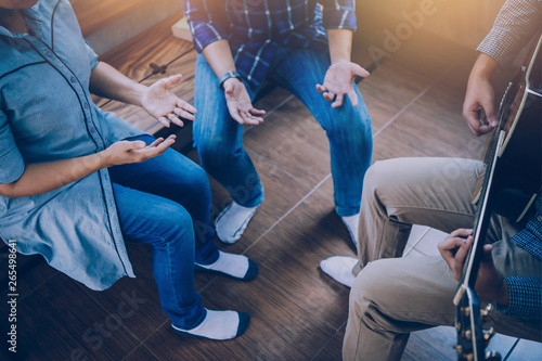Group of man and woman friends sitting on wooden chair while