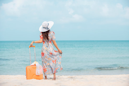 Relax  traveler woman in dress with sun hat holding suitcase standing on the beach  enjoys her tropical  vacation , lifestyle holiday travel  summer concept