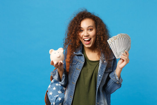 Young african american girl teen student in denim clothes, backpack hold pig isolated on blue wall background studio portrait. Education in high school university college concept. Mock up copy space.
