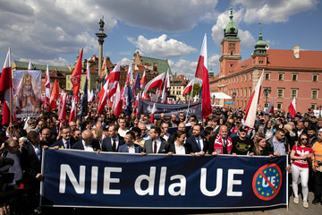 """People hold a banner reading """"No for EU"""" as they take part in a rally organised by far-right groups against the European Union in Warsaw as Central and Eastern European leaders gathered in the city for a summit marking 15 years since joining the European U"""