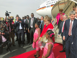 German Chancellor Angela Merkel poses for a picture as she arrives at the airport near Ouagadougo