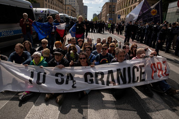 People seat and hold banner reading 'Here are the bounds of decency' as they block a rally organised by far-right groups against the European Union in Warsaw as Central and Eastern European leaders gathered in the city for a summit marking 15 years since j