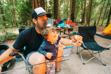Dad and son roasting marshmallows over propane fire at campsite