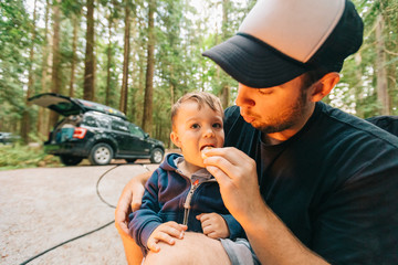 Father feeding son a roasted marshmallow at their campsite