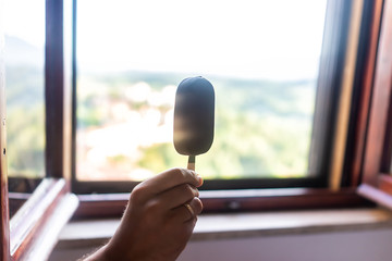 Hand holding one chocolate ice cream bar on stick with background of window during summer day in Italy with view