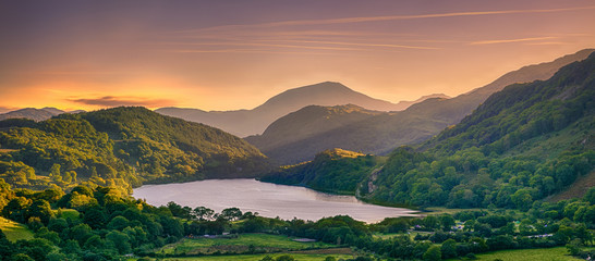 The Sun shining through a mountain pass over Llyn Gwynant, Snowdonia (Eryri), Wales (Cymru), UK