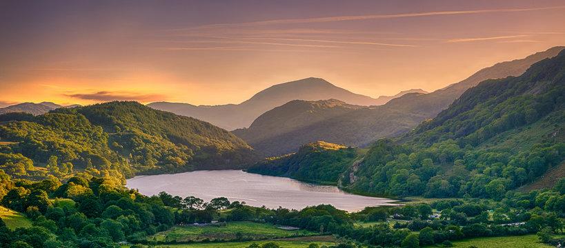 The Sun shining through a mountain pass over Llyn Gwynant, Snowdonia (Eryri), Wales (Cymru), UK