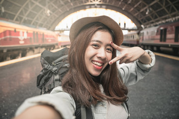Woman Traveler with backpack traveling taking picture self portrait with smartphone on her summer vacation. Summer Holiday Travel Destination concept. Fototapete