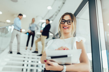 Beautiful business woman girl holding a tablet in her hands and smiling at the camera. In the background are business people. Wall mural