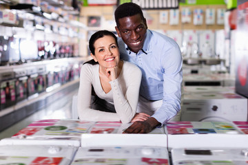 Portrait of smiling couple  standing  in  household appliances  store