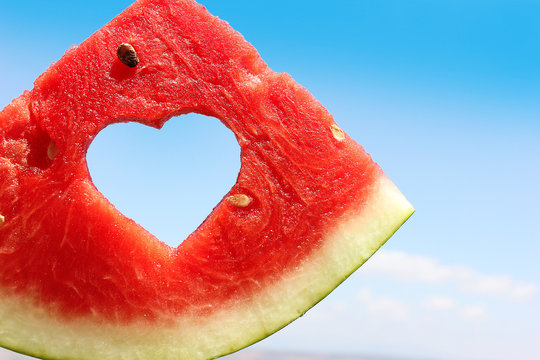 fresh slice of watermelon with heart inside on blue sky background