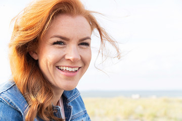 Friendly woman with red hair at the beach