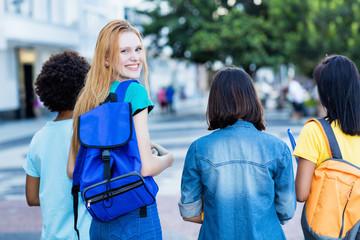 Junge Studentin mit roten Haaren und anderen Studenten