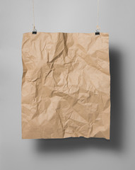 Brown crumpled paper sheet in holders with shadow on gray background,mock up empty paper blank