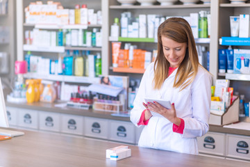 Portrait of pharmacist holding digital tablet in pharmacy. Electronic database. Top view of positive female pharmacist wearing uniform while using tablet