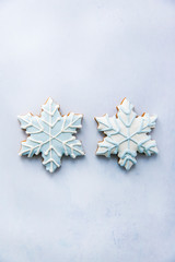 Two frosted gingerbread snowflake Christmas cookies