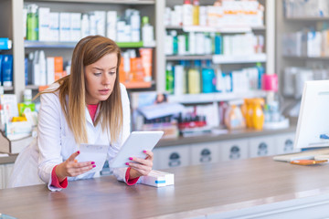 Image of woman  pharmacist using a digital tablet while checking medications in pharmacy. Pharmacist using a digital tablet in pharmacy