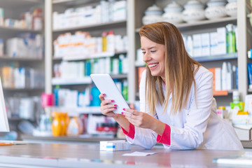 Young pharmacist holding a tablet and box of medications. Pharmacist holding computer tablet Using for filling prescription in pharmacy drugstore.