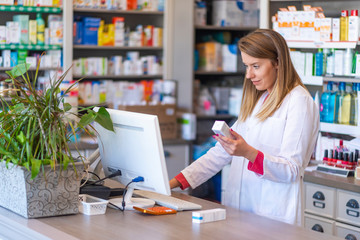 Female pharmacist working in chemist shop or pharmacy. Pharmacist using the computer at the pharmacy. Portrait of young female pharmacist holding medication while using computer at pharmacy counter