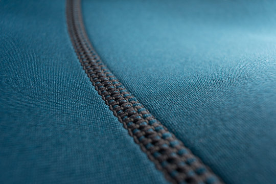 Close up of stitching along the seam of a blue neoprene scuba diving wetsuit