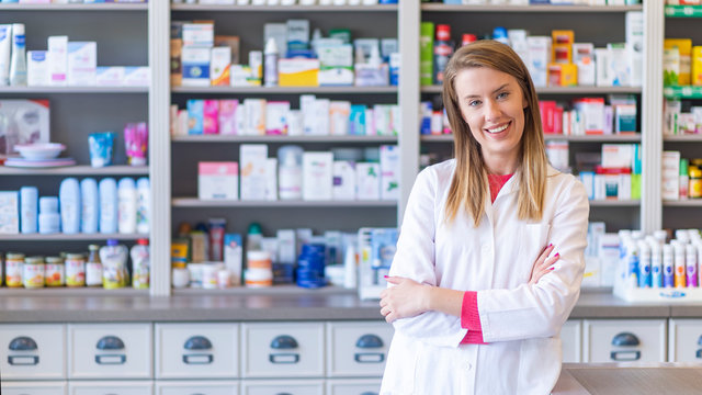 Portrait of a smiling pharmacist with arms crossed at modern pharmacy. Beautiful woman wearing in white lab coat working in drugstore.