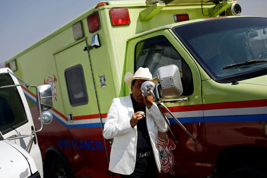 A man looks at himself in the mirror of an ambulance during the annual donkey festival as part of May Day events in Otumba