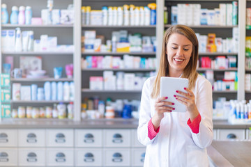 Portrait of pharmacist holding digital tablet in pharmacy. Pharmacist working with a tablet-pc in the pharmacy holding it in her hand while reading information