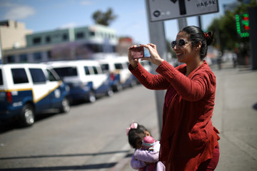 A woman takes pictures of drivers marching during May Day celebrations in Tijuana